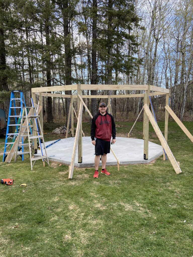 A picture of my son Josh after we got the main beams up, he was a big help.